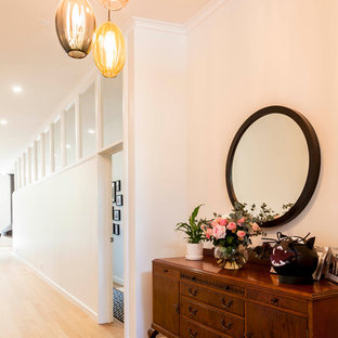 Mid-sized midcentury hallway in Melbourne with white walls, light hardwood floors and brown floor.