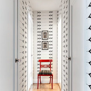 Photo of a small transitional hallway in Seattle with multi-coloured walls and medium hardwood floors.