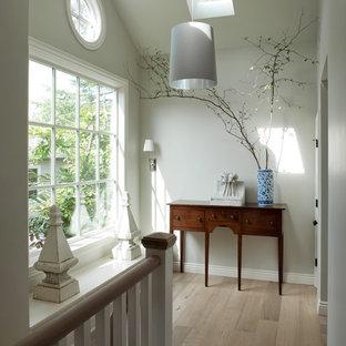 Foto de recibidores y pasillos tradicionales con paredes blancas, suelo de madera clara y suelo beige