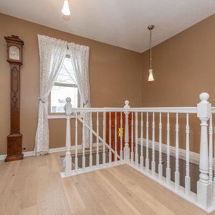 Mid-sized midcentury hallway in Minneapolis with beige walls, light hardwood floors and white floor.
