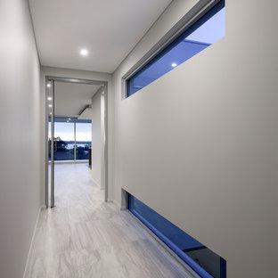 Пример оригинального дизайна: коридор среднего размера в стиле модернизм с белыми стенами и полом из керамогранита