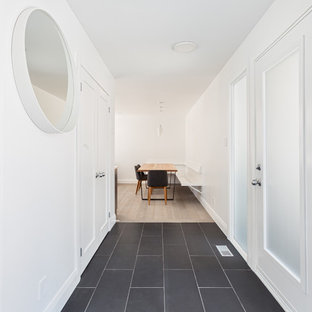 This is an example of a midcentury hallway in Toronto with white walls, porcelain floors and black floor.