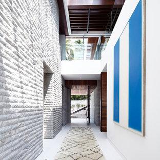 Réalisation d'un très grand couloir design avec un mur blanc et un sol en carrelage de céramique.