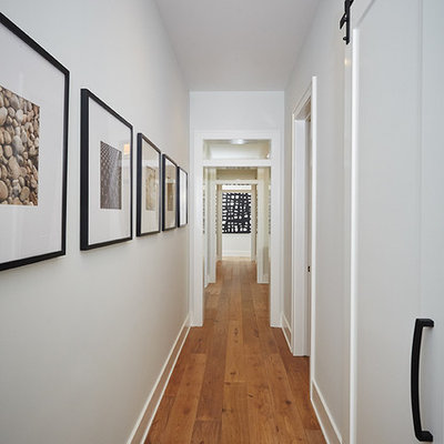 Large cottage medium tone wood floor hallway photo in Grand Rapids with gray walls