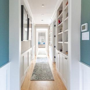Inredning av en lantlig stor hall, med blå väggar, ljust trägolv och beiget golv
