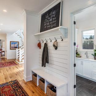 他の地域の広いカントリー風おしゃれな廊下 (白い壁、無垢フローリング、茶色い床) の写真