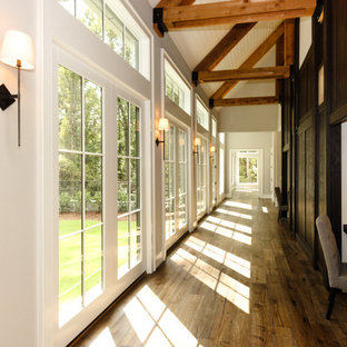 Mid-sized country medium tone wood floor hallway photo in Raleigh with beige walls
