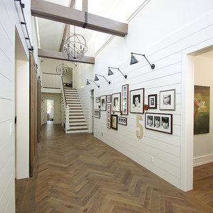 Cette image montre un grand couloir rustique avec un mur blanc, un sol en bois brun et un sol marron.