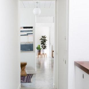 Cette image montre un couloir bohème avec un mur blanc et béton au sol.