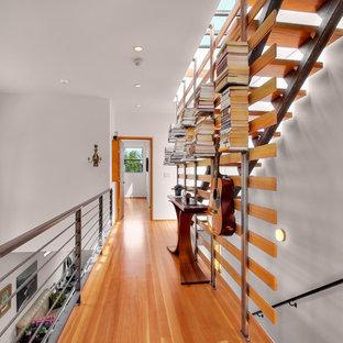 Cette image montre un couloir design avec un mur blanc, un sol en bois brun et un sol orange.