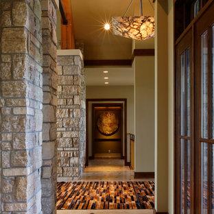 Exempel på en mycket stor modern hall, med beige väggar och kalkstensgolv