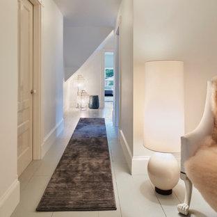 Ispirazione per un ingresso o corridoio minimal con pareti bianche, pavimento in legno verniciato e pavimento bianco