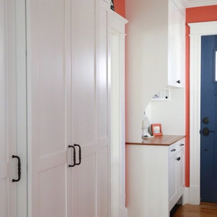 Mid-sized beach style hallway in Boston with light hardwood floors and red walls.