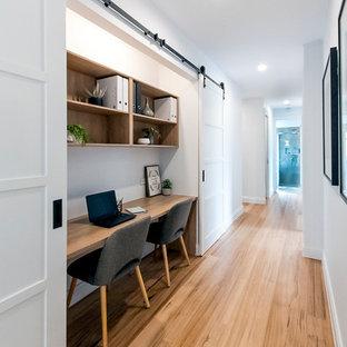 Idées déco pour un couloir campagne avec un mur blanc, un sol en bois brun et un sol marron.