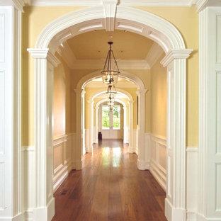 Источник вдохновения для домашнего уюта: огромный коридор в классическом стиле с желтыми стенами и паркетным полом среднего тона
