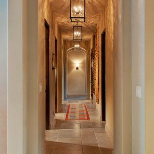 Exemple d'un grand couloir méditerranéen avec un mur blanc et un sol en travertin.