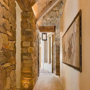 Ejemplo de recibidores y pasillos rústicos con paredes beige, suelo beige y suelo de madera clara