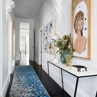Пример оригинального дизайна интерьера: коридор в современном стиле с белыми стенами, деревянным полом и черным полом