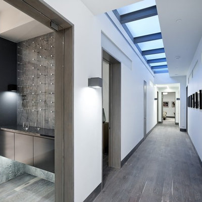 Example of a large trendy dark wood floor and gray floor hallway design in Denver with white walls