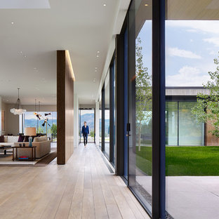 This is an example of a modern hallway in Denver with yellow walls and light hardwood floors.