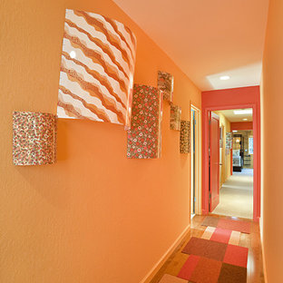 Inspiration for a contemporary medium tone wood floor and orange floor hallway remodel in San Francisco with orange walls