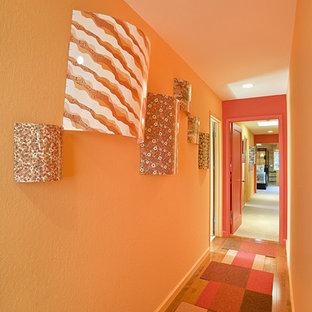 Идея дизайна: коридор в современном стиле с оранжевыми стенами, паркетным полом среднего тона и оранжевым полом