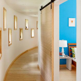 На фото: коридоры в современном стиле с белыми стенами и светлым паркетным полом