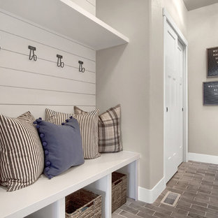 Cette image montre un couloir rustique de taille moyenne avec un sol gris, un sol en brique et un mur gris.