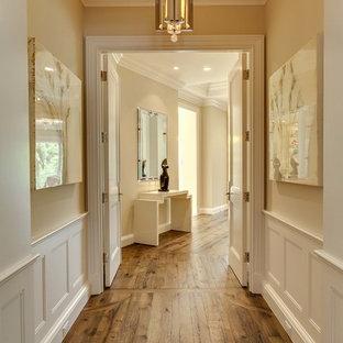 Exempel på en stor klassisk hall, med beige väggar, brunt golv och mellanmörkt trägolv