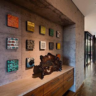 Exemple d'un grand couloir sud-ouest américain avec un mur gris, un sol en bois foncé et un sol marron.