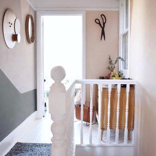Inspiration för små moderna hallar, med rosa väggar, målat trägolv och vitt golv