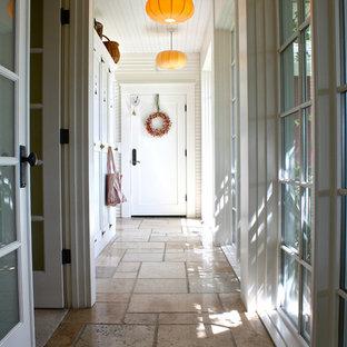 Cette image montre un couloir traditionnel avec un mur blanc et un sol en travertin.
