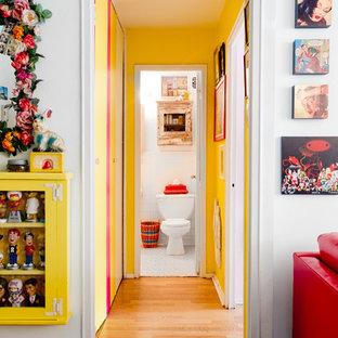 Создайте стильный интерьер: коридор в стиле фьюжн с желтыми стенами и паркетным полом среднего тона - последний тренд