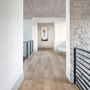 Cette photo montre un grand couloir moderne avec un mur blanc, un sol en bois brun, un sol marron, un plafond en bois et un mur en parement de brique.
