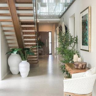 Exotisk inredning av en mellanstor hall, med vita väggar, klinkergolv i porslin och vitt golv