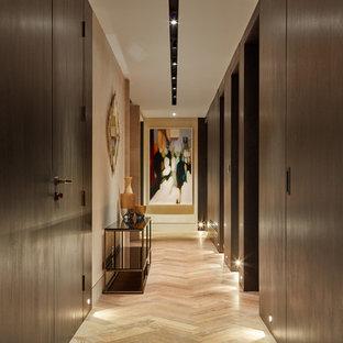 Diseño de recibidores y pasillos contemporáneos con paredes marrones, suelo de madera clara y suelo beige