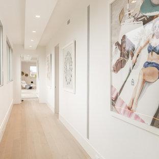 Trendy light wood floor and beige floor hallway photo in New York with white walls