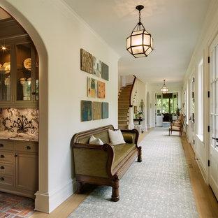 Large elegant light wood floor hallway photo in New York with white walls