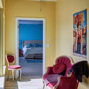 他の地域のトラディショナルスタイルのおしゃれな廊下 (磁器タイルの床、マルチカラーの床、黄色い壁) の写真