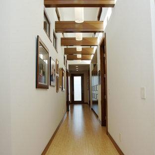 Foto på en funkis hall, med vita väggar och bambugolv