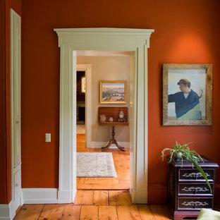 フィラデルフィアのトラディショナルスタイルのおしゃれな廊下 (赤い壁、無垢フローリング、オレンジの床) の写真