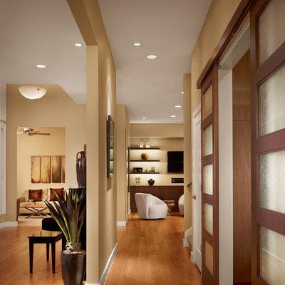 Mid-sized trendy medium tone wood floor and brown floor hallway photo in Austin with beige walls