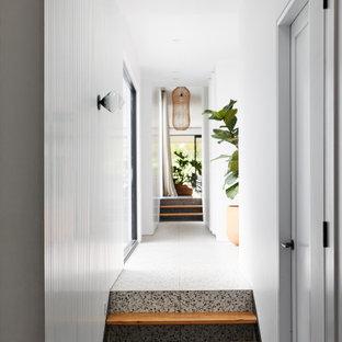 На фото: большой коридор в современном стиле с белыми стенами, бетонным полом, черным полом и панелями на части стены с