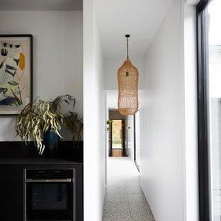 Foto de recibidores y pasillos modernos, grandes, con paredes blancas, suelo de cemento y suelo negro