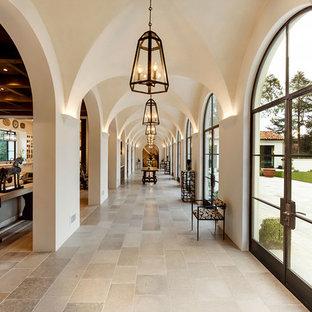 На фото: огромный коридор в средиземноморском стиле с белыми стенами, полом из известняка и серым полом с