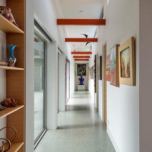 Inspiration pour un couloir vintage avec un mur blanc, un sol gris et un plafond en poutres apparentes.