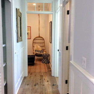 This is an example of a mid-sized beach style hallway in Miami with grey walls, light hardwood floors, brown floor, recessed and decorative wall panelling.