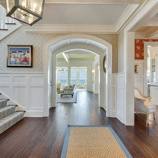 This is an example of an expansive beach style hallway in New York with multi-coloured walls, dark hardwood floors and brown floor.