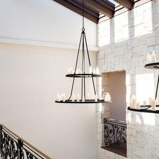 Réalisation d'un grand couloir méditerranéen avec un mur blanc, un sol en bois foncé, un sol marron et un plafond voûté.