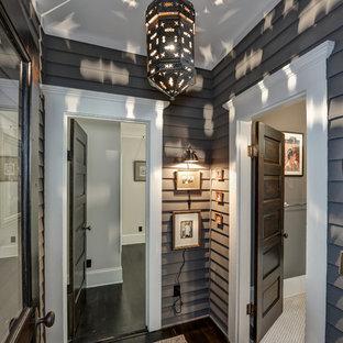 Aménagement d'un petit couloir avec un mur gris et un sol en bois foncé.